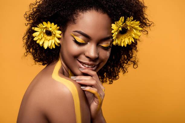 frau mit künstlerischen make-up und gerbera in haar - blumen make up stock-fotos und bilder