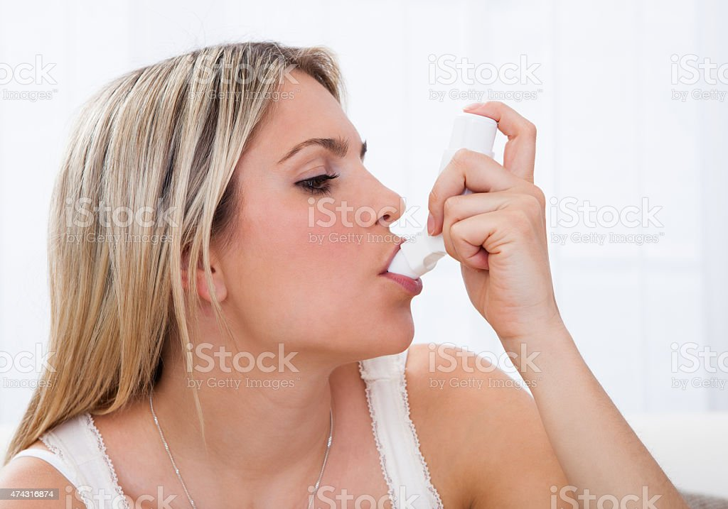 Woman with asthma inhaler stock photo