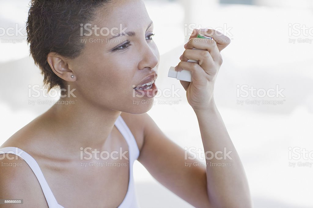 Woman with asthma using inhaler royalty-free stock photo