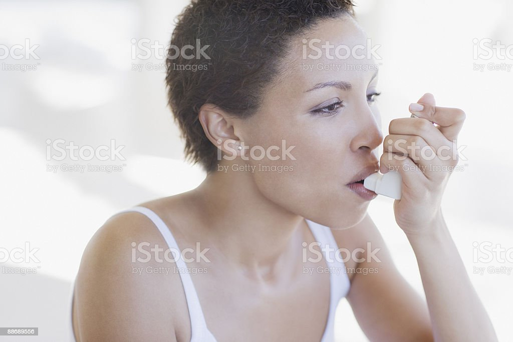 Woman with asthma using inhaler stock photo