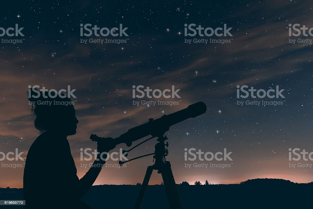 Woman with astronomical telescope. Night sky, with clouds and constellations stock photo