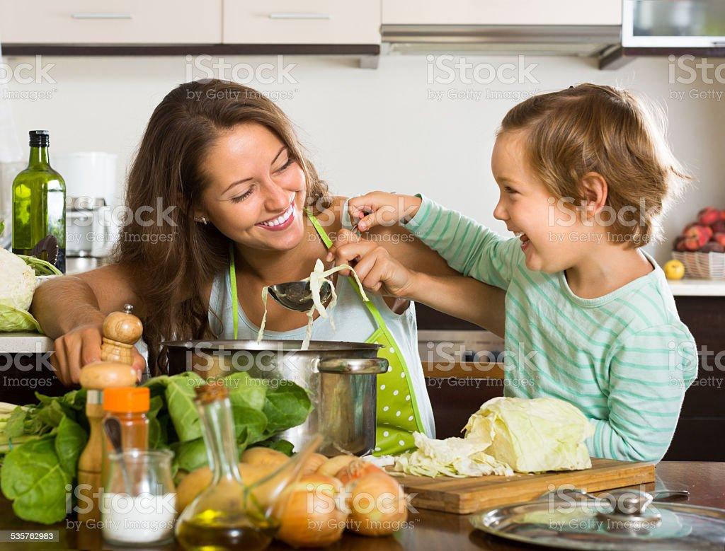 Mulher com bebê cozinhar na cozinha - foto de acervo