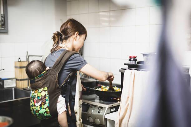 台所で赤ちゃんの料理を持つ女性 - 女性会社員 ストックフォトと画像