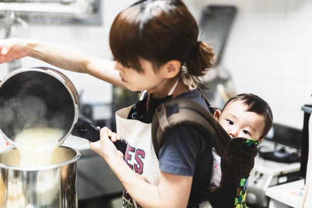 mulher com o bebê que cozinha na cozinha - foto de acervo