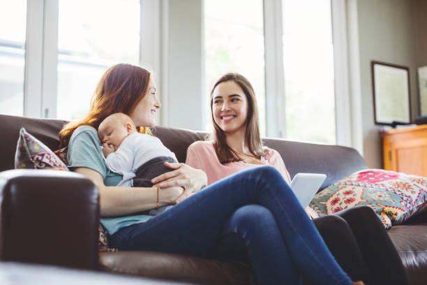Mujer con bebé hablar con amiga - foto de stock