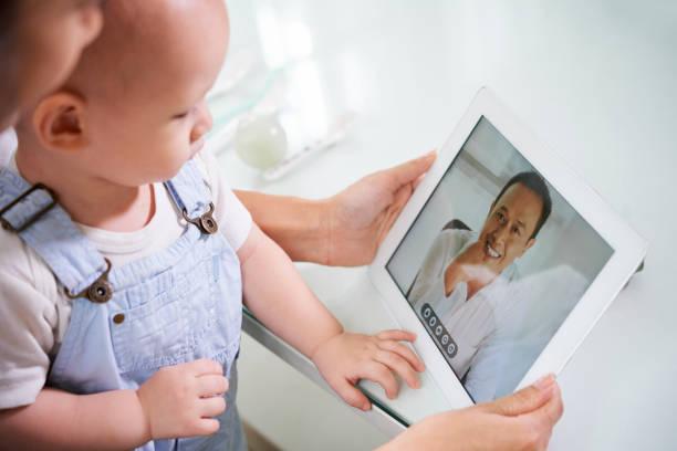 mujer con bebé video llamando marido - telehealth fotografías e imágenes de stock