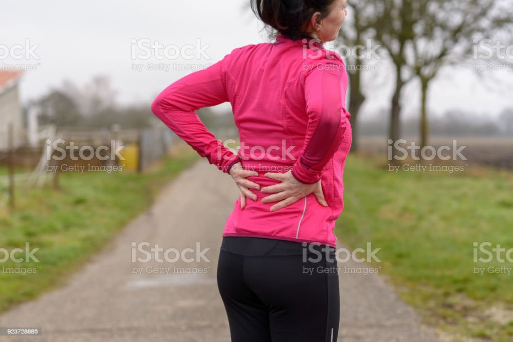 Woman with back or kidney pain clutching her back stock photo
