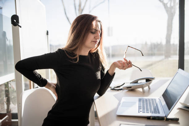 Woman with back pain in the office stock photo