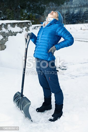 Senior woman has backache from clearing snow with a snow shovel