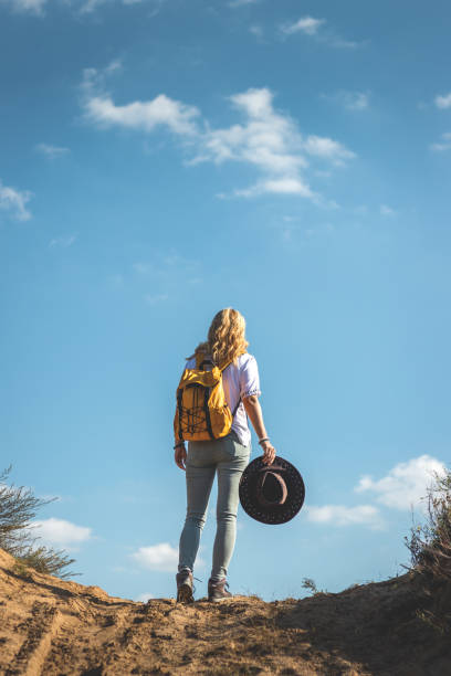 Woman with backpack and hat standing outdoors against blue sky stock photo