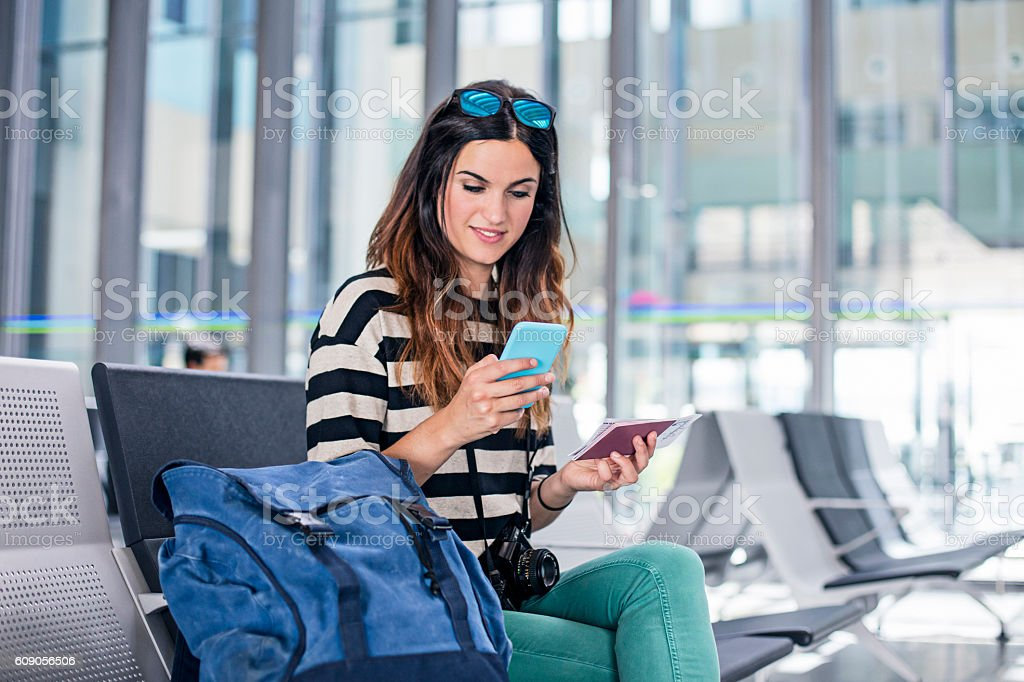 Woman with backpack and mobile phone waiting for boarding stock photo