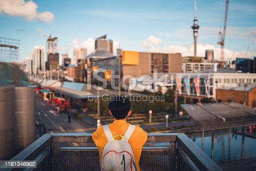 Woman with backpack enjoying Auckland city view.