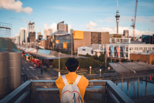 Woman with backpack enjoying Auckland city view. stock photo