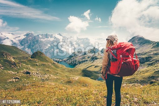 istock Woman with backpack enjoying mountains landscape view hiking 611212896