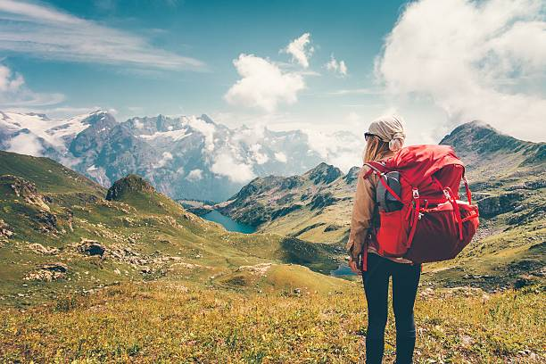 Woman with backpack enjoying mountains landscape view hiking stock photo