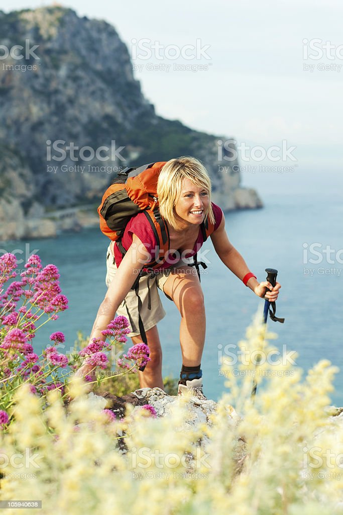 Woman with backpack, hiking along a rugged coast stock photo