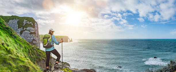 Woman with backpack hiking at coastal trail in Normandie Woman with backpack hiking at coastal trail in Normandie Panoramic View dieppe france stock pictures, royalty-free photos & images