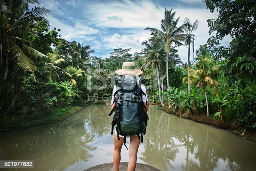 istock Woman with backpack near tropical river 521977832