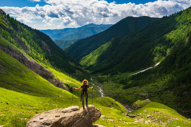 Woman with backpack resting on mountain top, looking at view dramatic landscape valley summer activity fitness wellbeing freedom concept, rear view stock photo