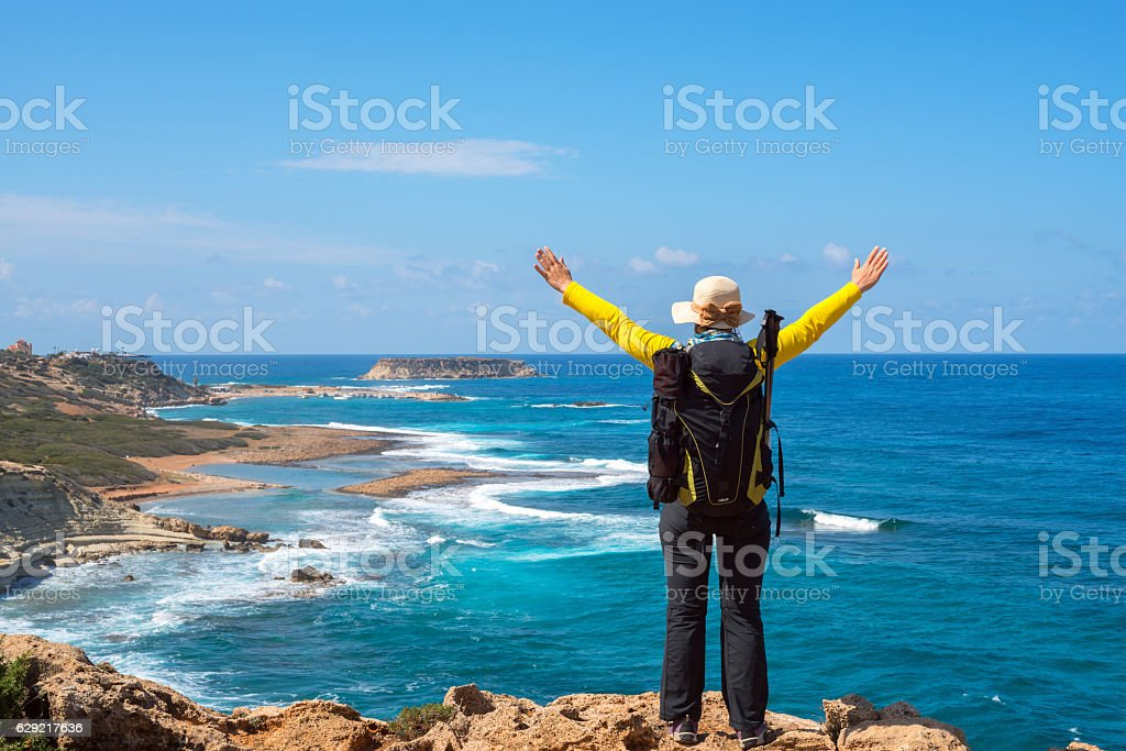 Woman with backpack standing on the seashore stock photo