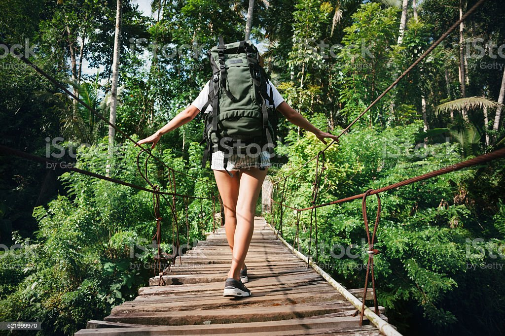 Woman with backpack traveling across bridge stock photo