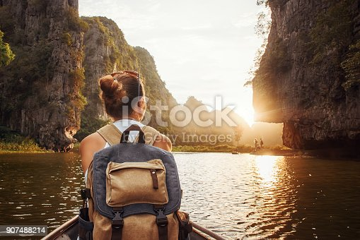 istock woman with backpack traveling by boat enjoying sunset among of mountains. 907488214