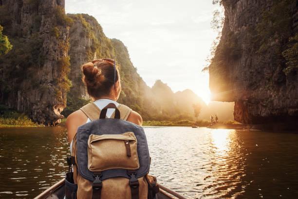 vrouw met rugzak reizen per boot genieten van de zonsondergang onder van bergen. - vietnam stockfoto's en -beelden