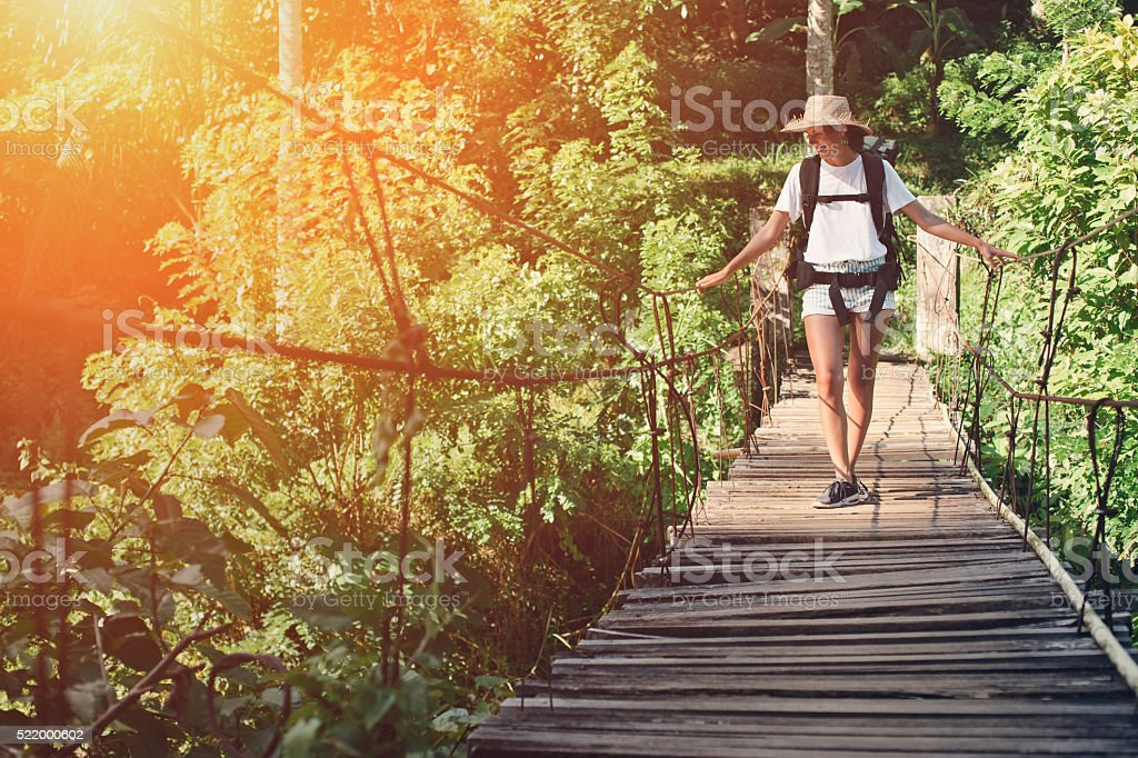 Woman with backpack traveling over hanging bridge stock photo