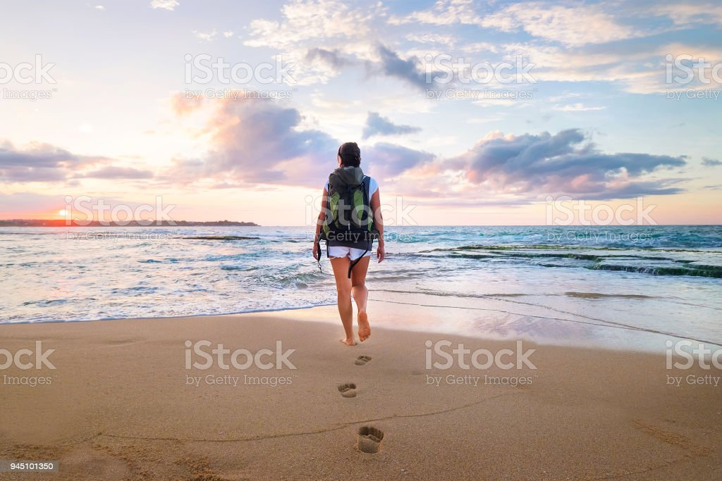 5120a34c5 Mujer con mochila caminar en la playa de arena de mar en el atardecer foto  de