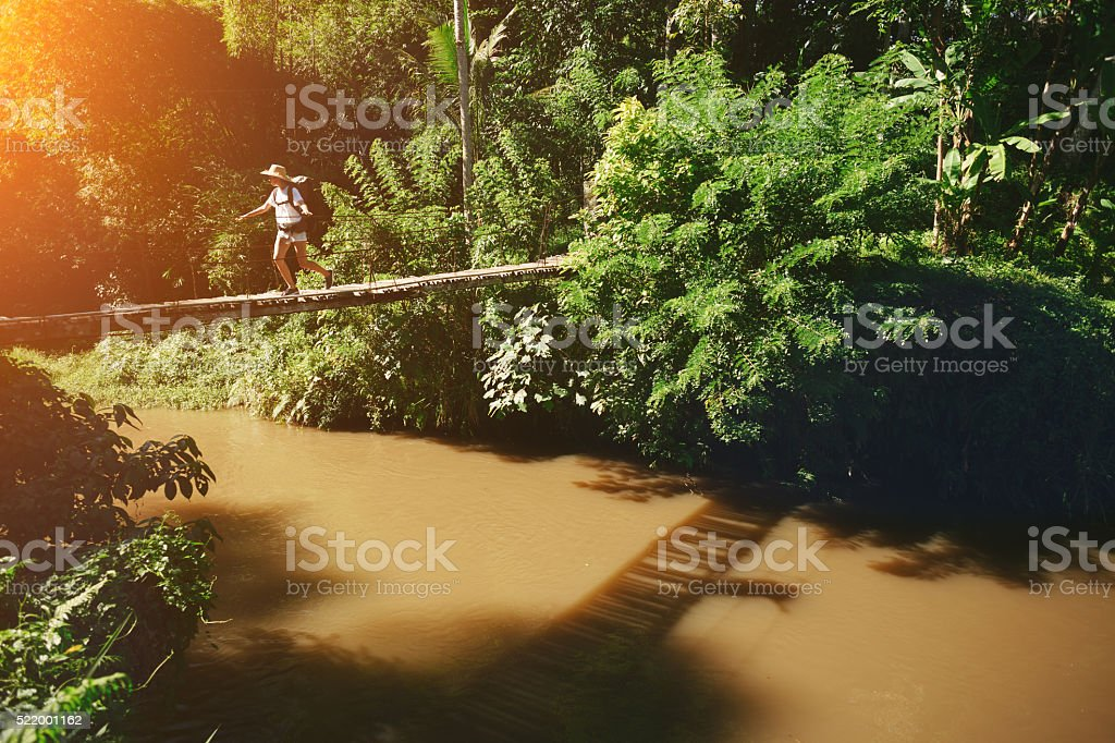 Woman with backpack walking across hanging bridge above the river stock photo