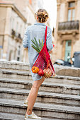 istock Woman with bag full of food walking outdoors 846085970