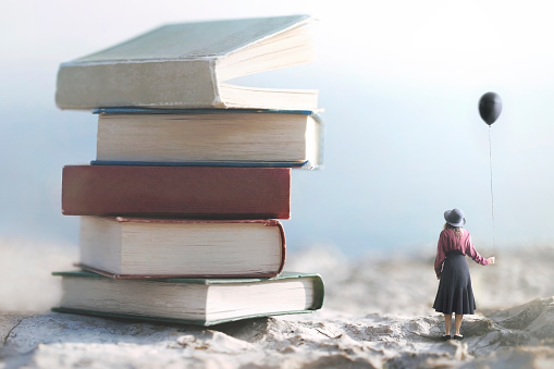 istock woman with balloon looks amazed at a mountain of giant books 1071661232