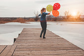 Woman with balloons by frozen lake