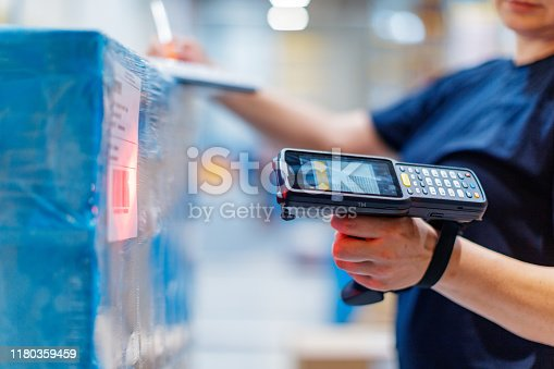 Woman in warehouse aiming at product, holding barcode reader
