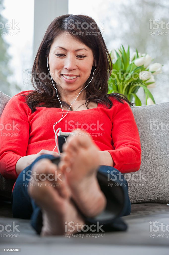woman with bare feet on sofa listening to mp3 player stock photo