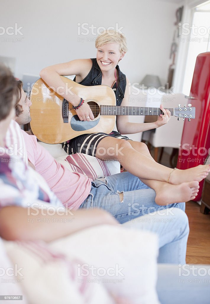 Woman with bare feet playing guitar for men on sofa royalty-free stock photo