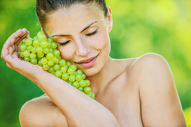 woman with bare shoulders holding grapes stock photo