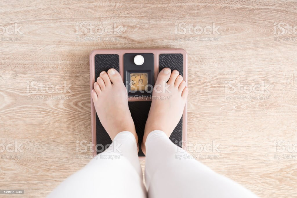Woman with barefoot standing on the scales. New start for healthy nutrition, body slimming, weight loss. Cares about body concept. Top view. stock photo