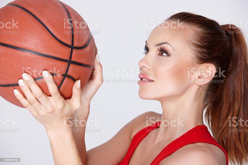 Beautiful and sporty woman holding basket ball