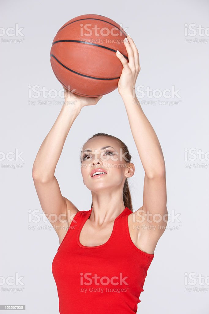 Beautiful and sporty woman throwing basket ball