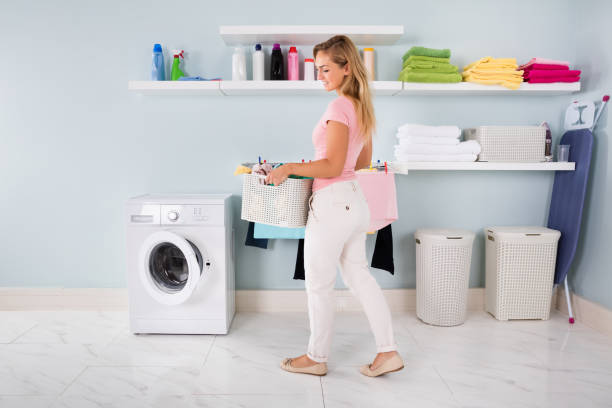 woman with basket of clothes in utility room - laundry laundry room stock pictures, royalty-free photos & images