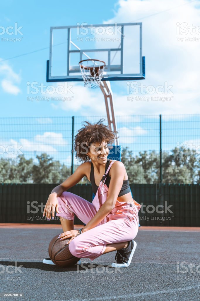 young african-american woman in sports bra and pink overalls...