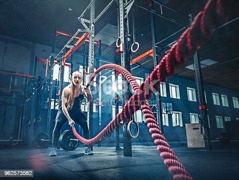 istock Woman with battle rope battle ropes exercise in the fitness gym 962573582