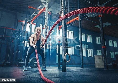 istock Woman with battle rope battle ropes exercise in the fitness gym 962573798