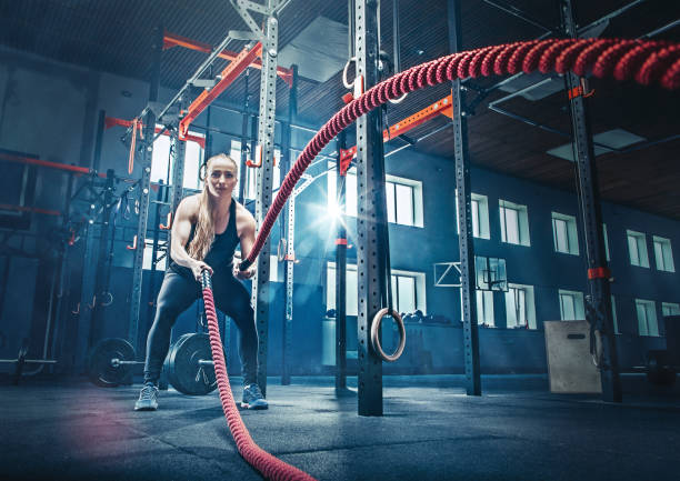 Woman with battle rope battle ropes exercise in the fitness gym stock photo