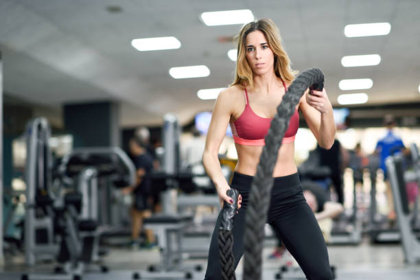 Woman with battle ropes exercise in the fitness gym. stock photo