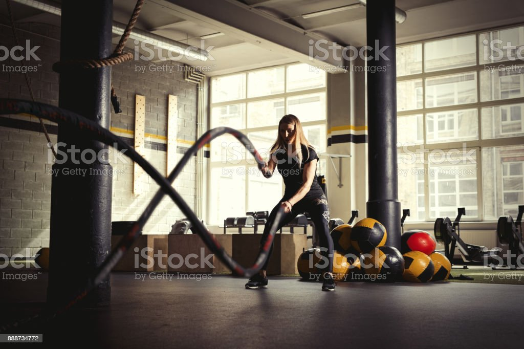 Woman with battle ropes in gym. stock photo