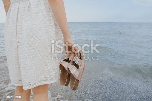 woman in a white dress holds beach slippers in her hands and walks along the shore of the blue sea