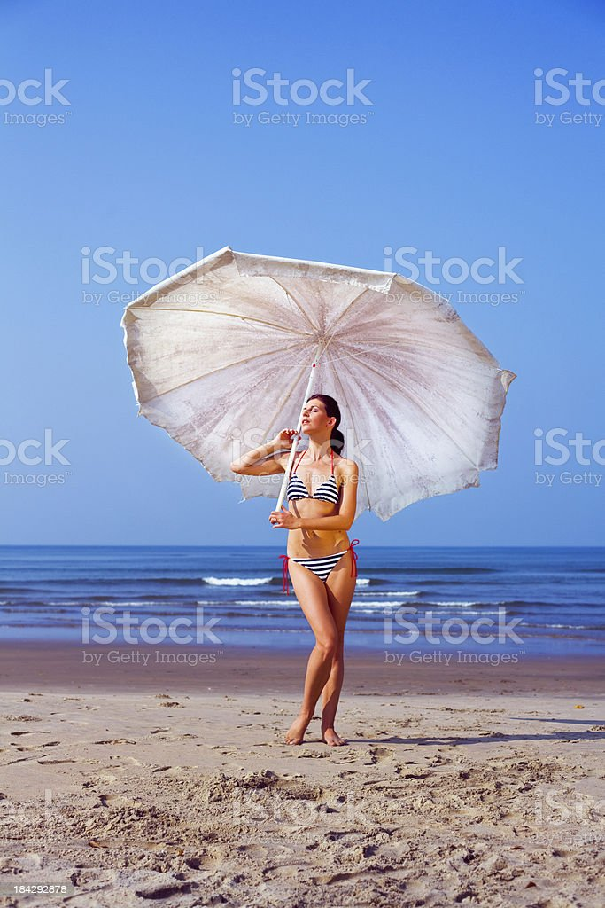 Woman with beach umbrella Summer portrait of beautiful woman wearing striped bikini standing on sand and holding a big beach umbrella in her hand.  25-29 Years Stock Photo