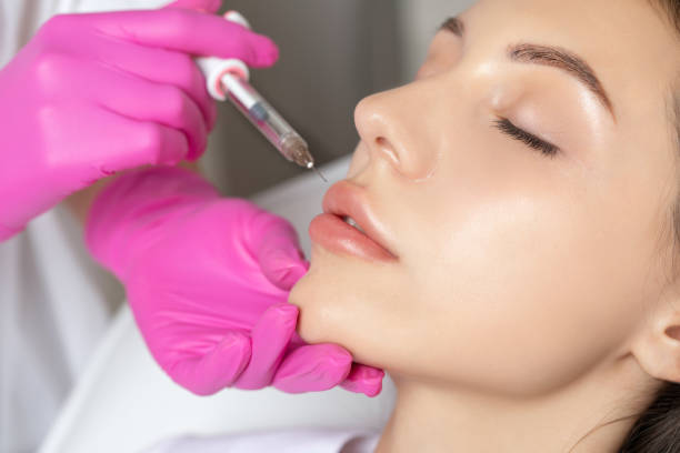 Woman with beautiful clean skin. Cosmetologist does injections for lips augmentation and anti wrinkle of a beautiful woman. Women's cosmetology in the beauty salon. stock photo